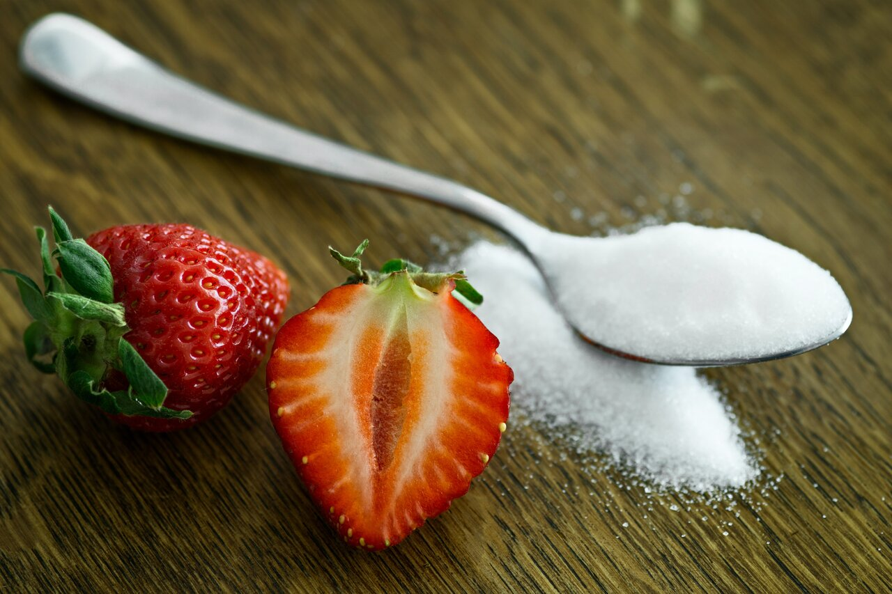sugar on a spoon next to a strawberry