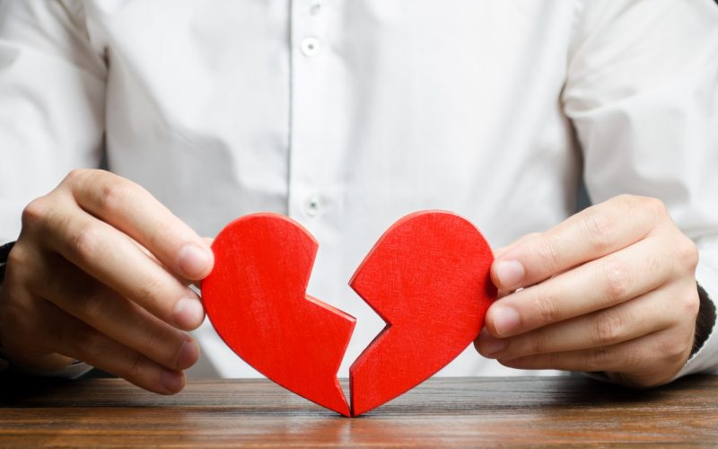 A man collects a broken heart in his hands. Concept of love and relationships. Family psychotherapist services. Reconciliation. Saving the family. Search for compromises. Search for the second half.