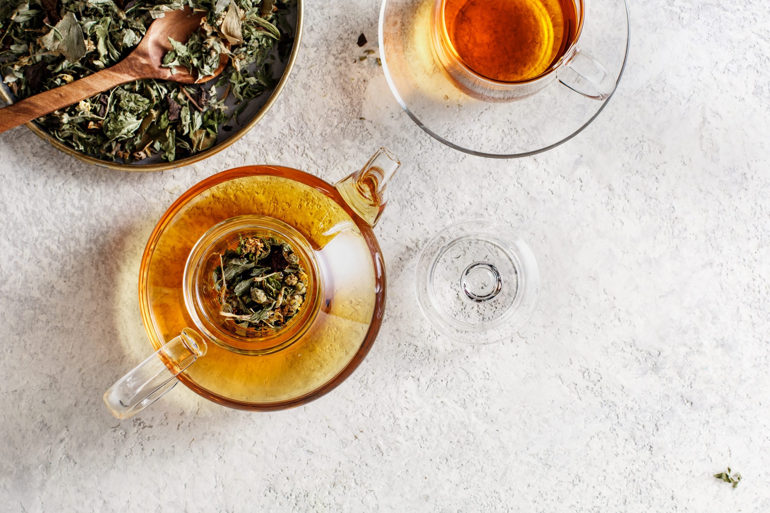 Glass teapot and a teacup with herbal tea.